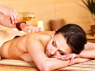Woman getting massage in bamboo spa.