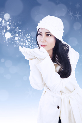 Beautiful woman blowing snowflakes on blue background