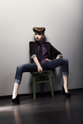 Pin-up girl sitting in jeans and stylish jacket. Bright hairstyle