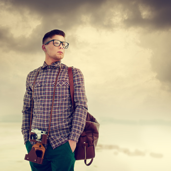 young man with a camera, dressed in the style of hipster