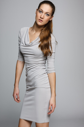 Elegant woman in gray dress posing in studio