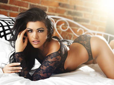 beautiful dark haired girl in sexy lingerie posing on bed