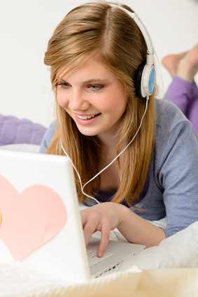 Young teenage girl chatting on laptop