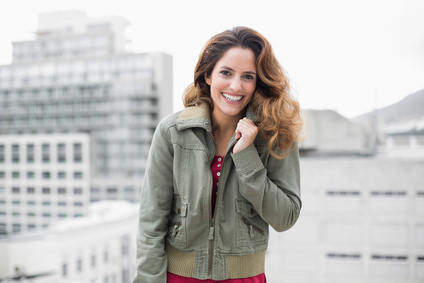 Cheerful gorgeous brunette in winter fashion looking at camera on urban background