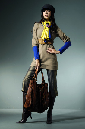 Attractive young fashion model in hat with hand bag