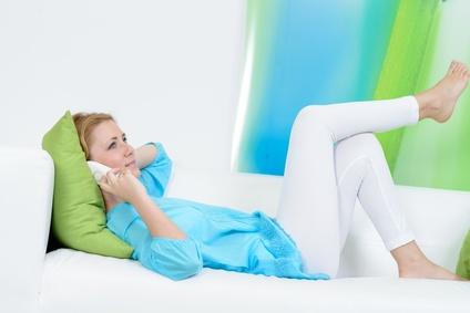 frau liegt relaxt auf dem sofa und telefoniert