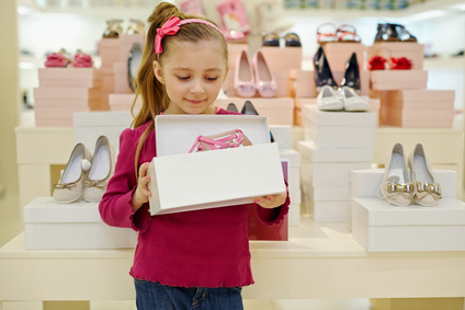 Little girl stands and holds open box with pink shoes