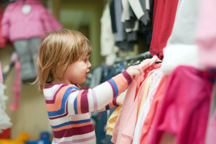 baby girl chooses clothes at shop