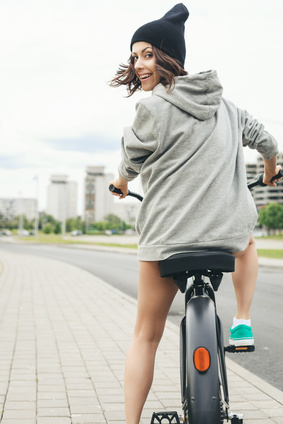 Young hipster girl with black bike